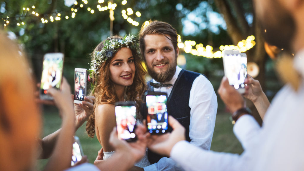 Bride and groom being photographed by guests on multiple mobile phones